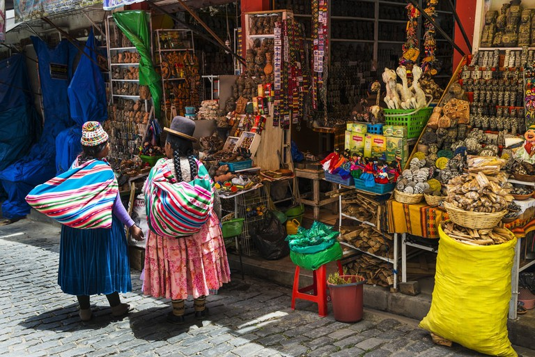 Local woman wearing traditional clothing in front of a store in a street in La Paz, Bolivia | © Peek Creative Collective/Shutterstock