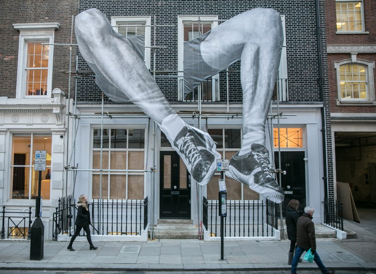 Installation of legs coming out of a building in Mayfair by French Street artists JR