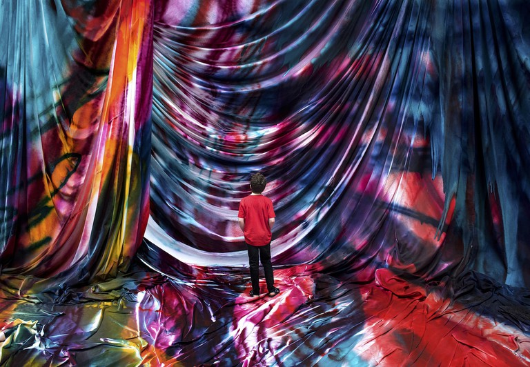 Boy looks at the German painter Katharina Grosse's immersive installation of colourfully painted fabric at Carriageworks in Sydney