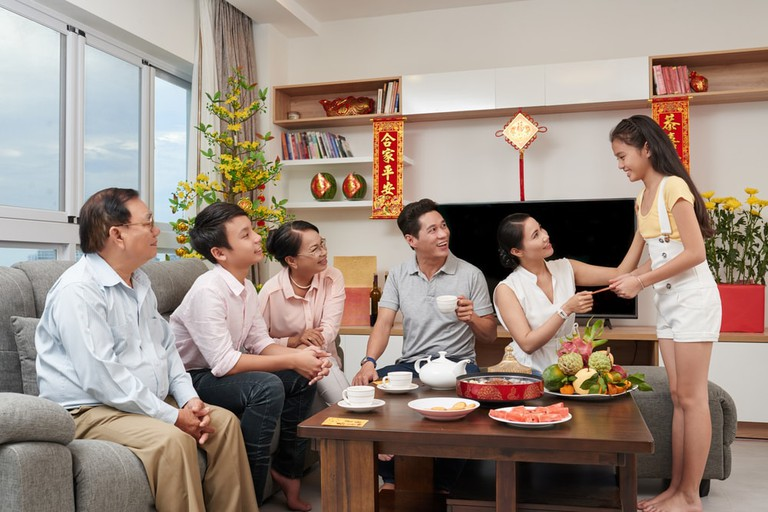 Fruit trays, family and lucky money   © Dragon Images/Shutterstock