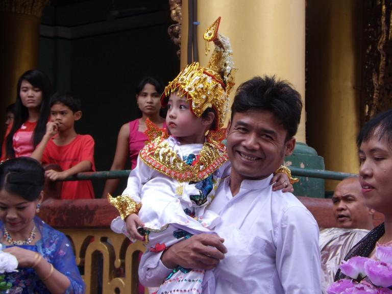 Myanmar-Yangon-local-Shwedagon-Pagoda-man-carrying-child-in-traditional-dress