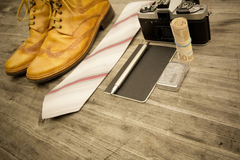 Hipster boots, tie, camera, notepad, pen, lighter, and money