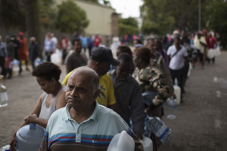Residents wait in a queue to fill containers with water at a source for natural spring water in Cape Town