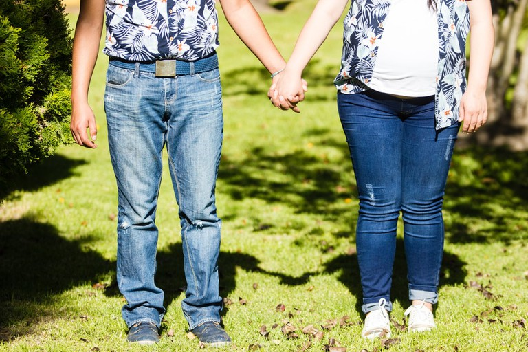 Couple holding hands wearing matching outfit jeans and blue shirt | © Cris_mh/Shutterstock