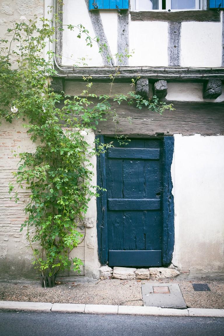 Blue painted wooden door in Eymet, France   © Kelsey Hayne/Shutterstock