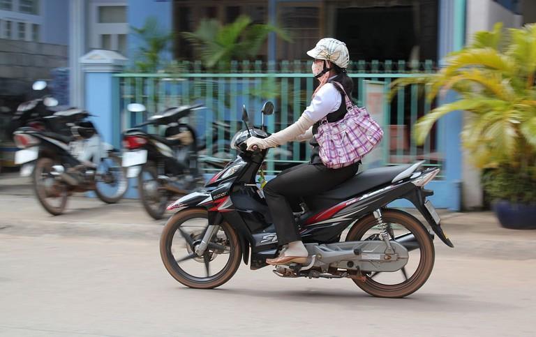 1280px-Female_motorcyclist_wearing_gloves,_Phú_Quốc,_Vietnam