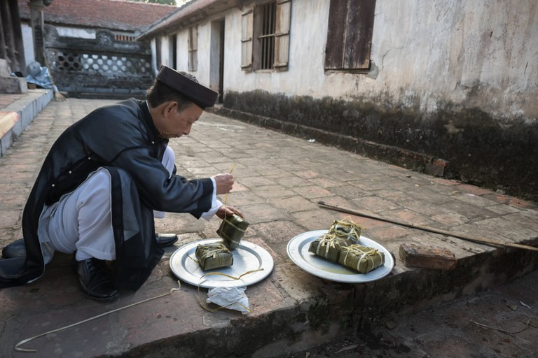 A man takes Chung cake out of cooking pot at So village, Quoc Oai district
