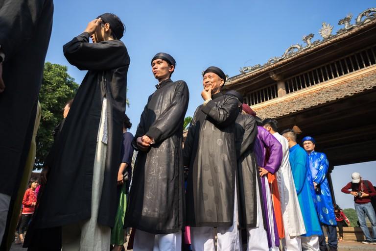 Vietnamese men wear traditional long dress Ao Dai