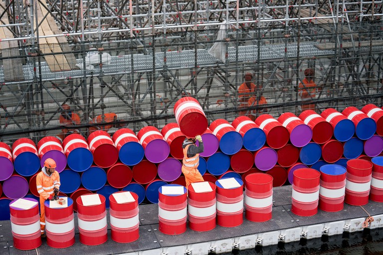 The London Mastaba - Workers installing barrels on the vertical side of the London Mastaba