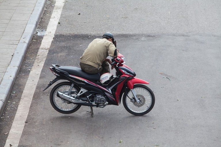A motorcycle driver (motor taxi) waiting for passenger, Hanoi