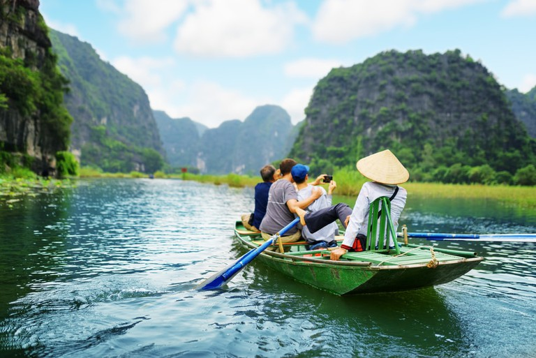 Tourists traveling in boat along the Ngo Dong River, Vietnam