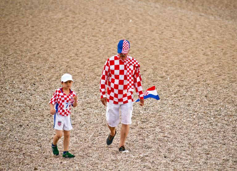 Grandfather and grandson celebrating Croatian football team win