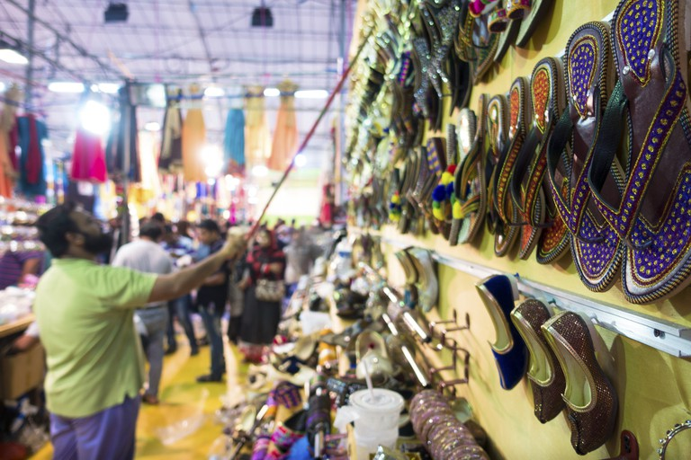 A shop owner man restocks colorful shoes on the wall at a night market during the Deepavali festival.