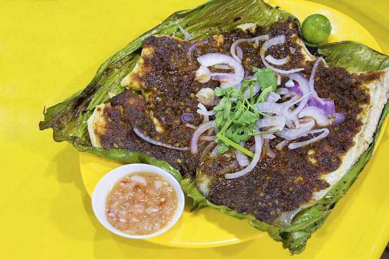 Stingray Fish with Sambal Chili Paste Sauce with Chopped Onions Cilantro and Fermented Shrimp Dipping Sauce.