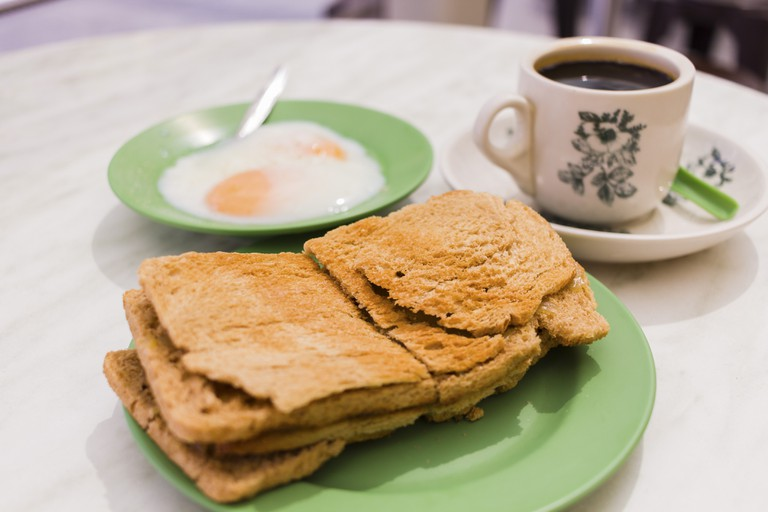 Singapore Breakfast called Kaya Toast, Coffee bread and Half-boiled eggs, which includes Chinese coffee in vintage mug and bread toast with a local jam made from eggs, sugar and coconut milk.