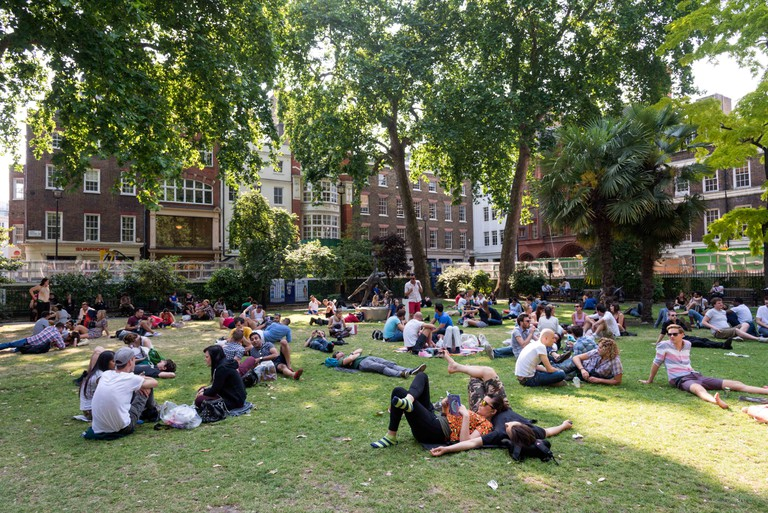 People relaxing in Soho Square, London, England, UK