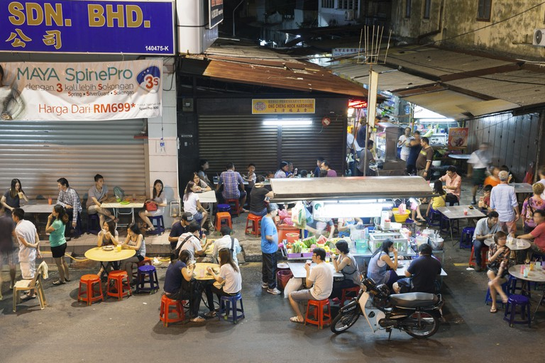 The crowd of people dining at the street food stalls on Lebuh Chulia in historic part of Chinatown in, Georgetown, Malaysia.