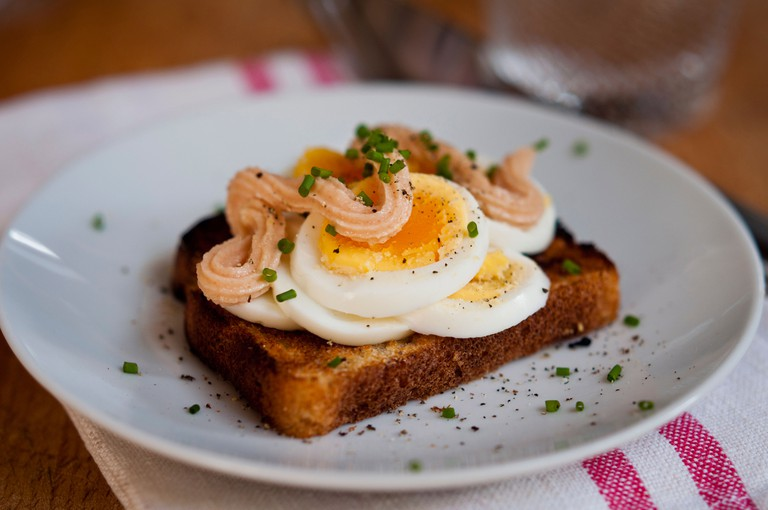 Classic Swedish open faced sandwich of sliced boiled egg topped with Kalle's kaviar and sprinkled with chopped chives.