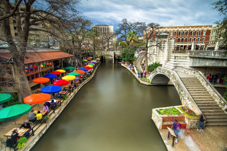 Part of the San Antonio riverwalk with buildings and restaurants lining the river