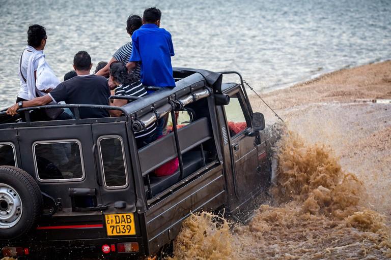 Jeep driving through deep water on safari in Minneriya National Park, Sri Lanka taken on 16 September 2016
