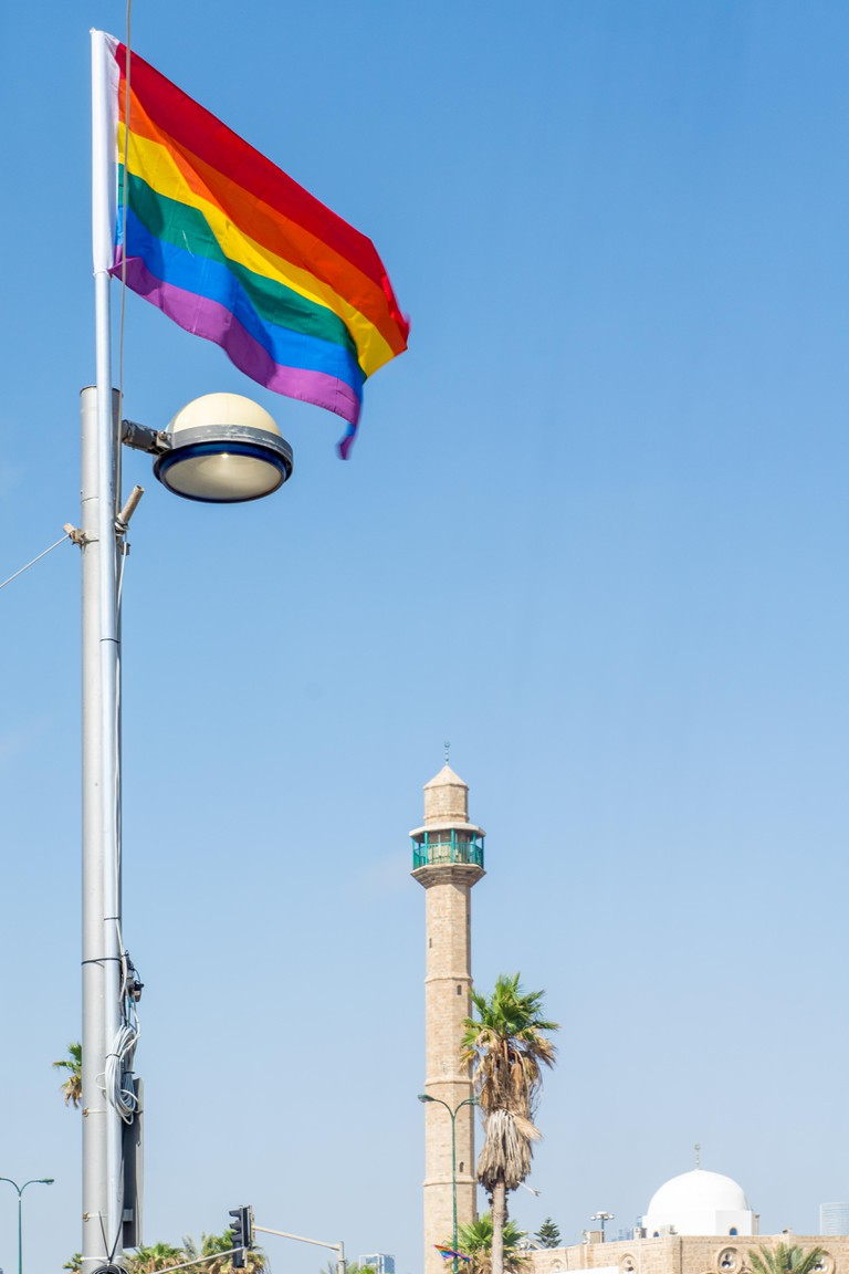 The minaret of Hassan Bek Mosque and a pride rainbow flag, in the day of the Pride Parade, in Tel-Aviv, Israel
