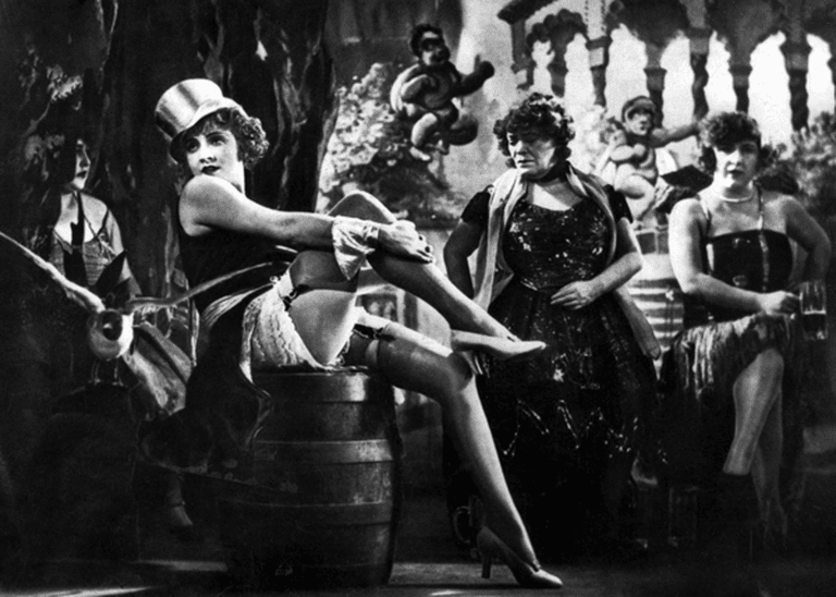 """<a href=""""https://en.wikipedia.org/wiki/Weimar_culture#/media/File:Marlene_Dietrich_in_The_Blue_Angel.png"""">A publicity photograph for the film <i>Der Blaue Engel</i> (The Blue Angel) 1930, featuring Marlene Dietrich   © Wikimedia Commons</a>"""