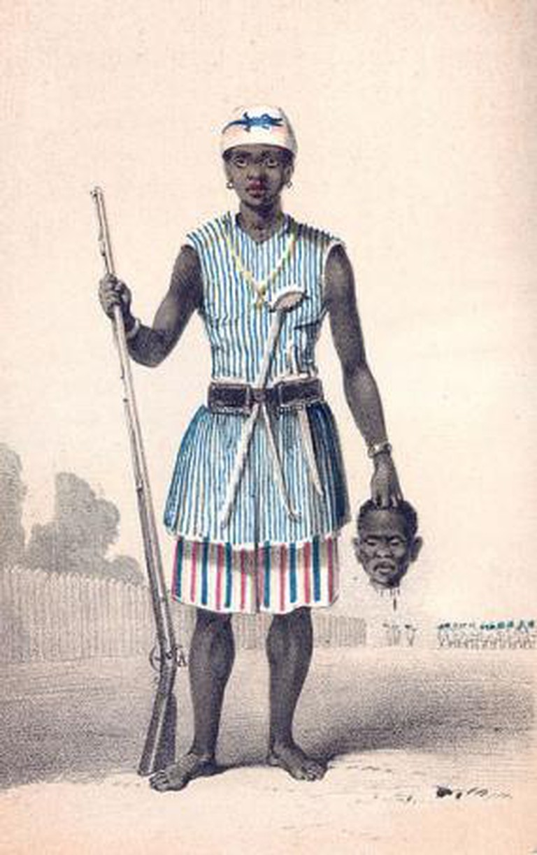 A Dahomey Warrior holding a head and a spear