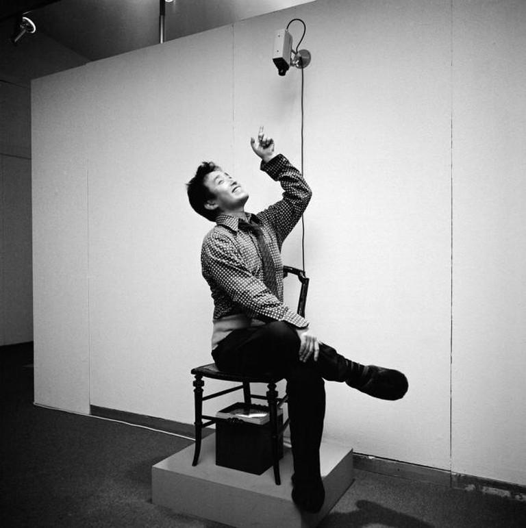 """Paik sitting in TV Chair (1968/1976) in """"Nam June Paik Werke, 1946–1976: Music, Fluxus, Video,"""" 1976"""