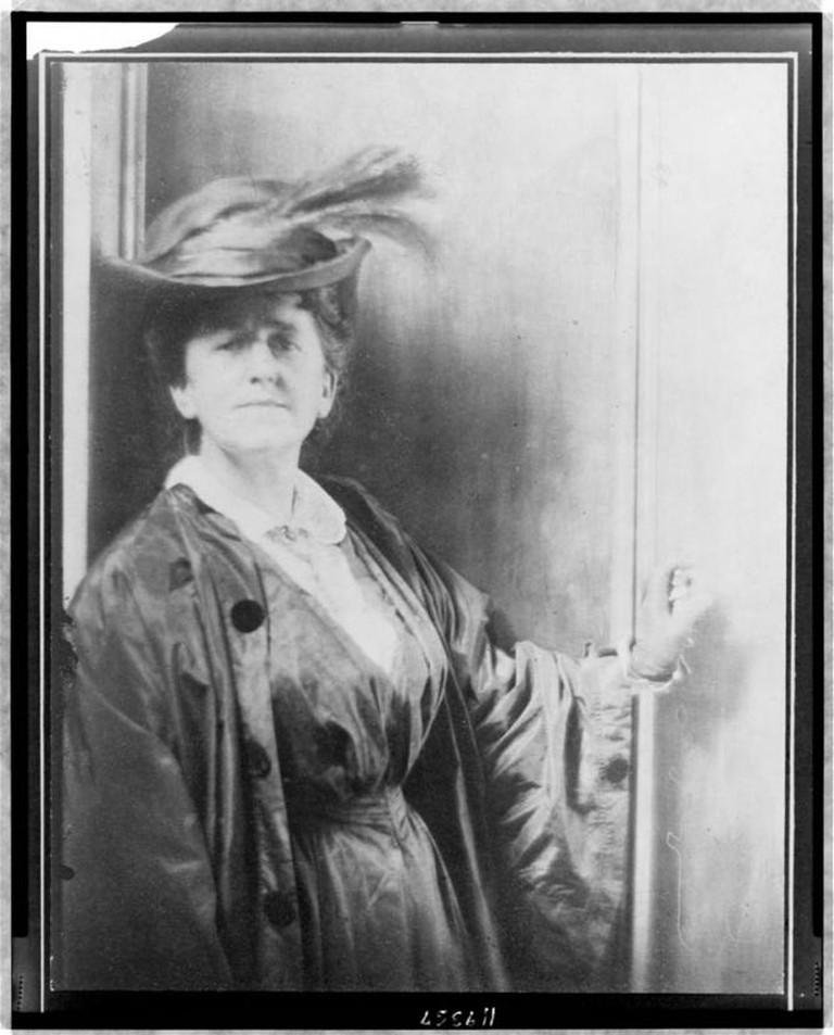 Baron Adolf De Meyer, Gertrude Käsebier, wearing feathered hat, standing, facing front, half-length portrait, c. 1900