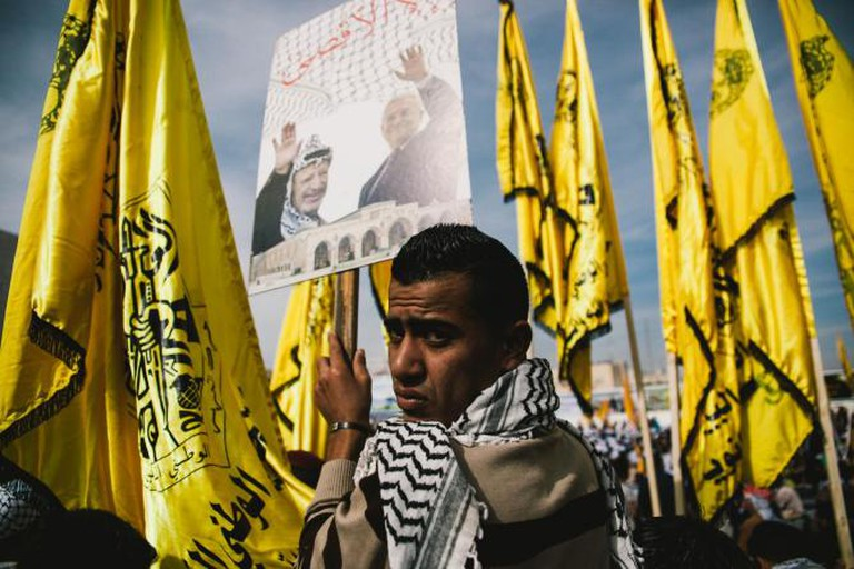 A young man holds a sign showing the former Yasser Arafat and the current president Muhammad Abu Abbas, on the tenth anniversary of the passing of Yasser Arafat in the West Bank town of Ramallah.