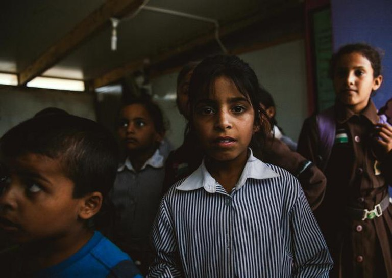 A bedouin girl stands with classmates on the last day of school before the start of eid al adha.