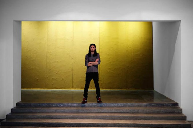 Kour Pour in front of his work at his Los Angeles solo exhibition at Depart Foundation