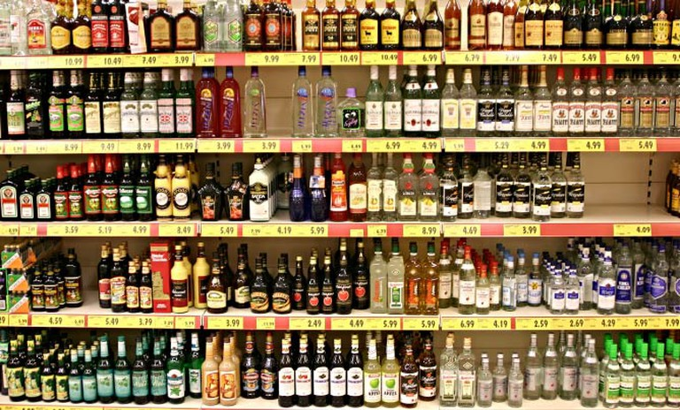 A wall lined with different types of liqeur and alcohol