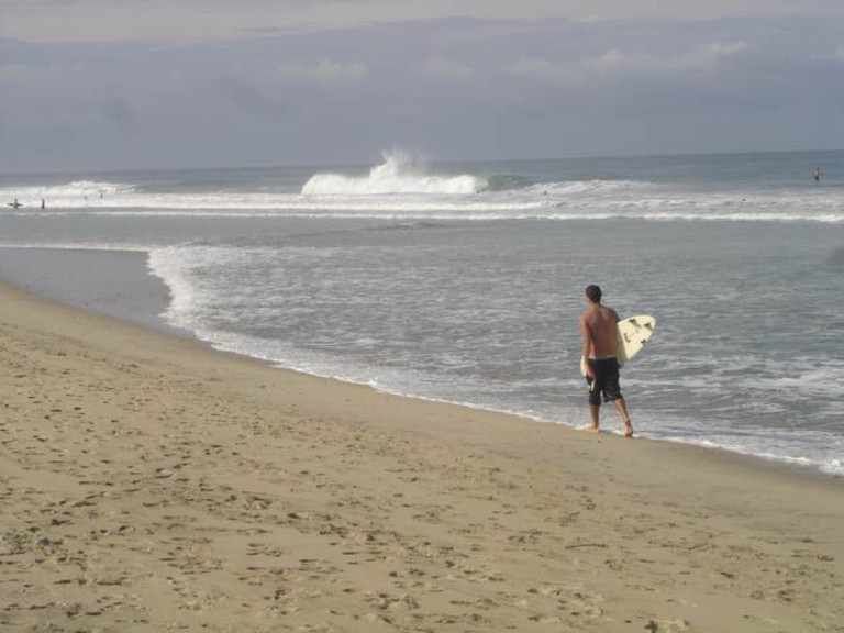 Surfer walking down the beach of Puerto Escondido