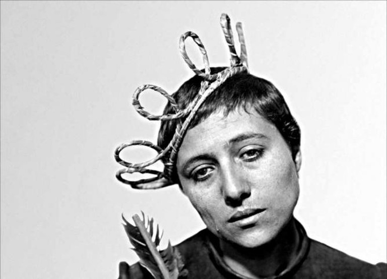 A crying woman with a straw crown tilts her head to the side.