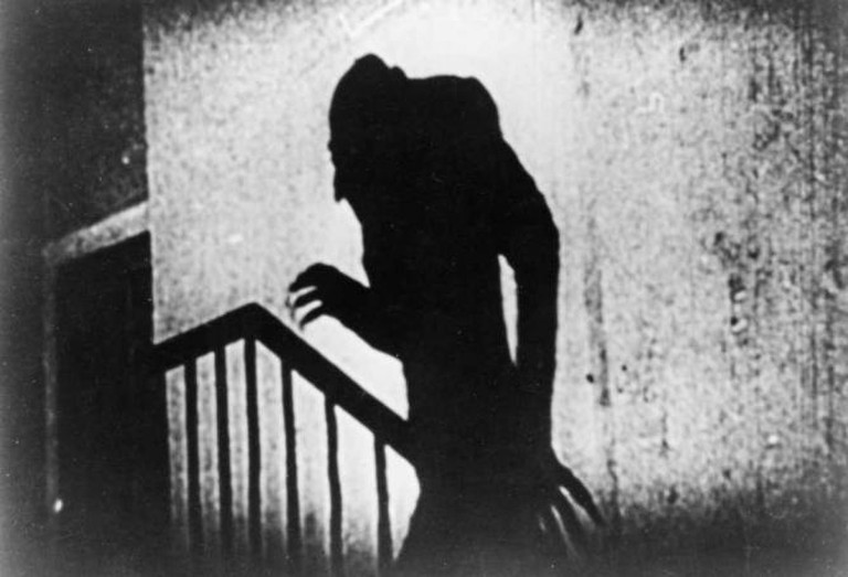 A shadow with long fingers and an unusual facial profile walks up the stairs