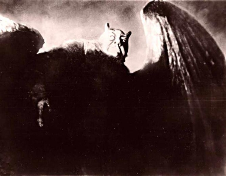 A demon-like creature with wings looks off into the distance