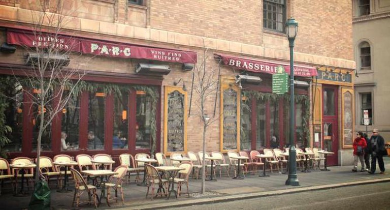 Parc Brasserie sits on the corner of Locust St and 18th on a winter day as pedestrians stroll along its outdoor tables.