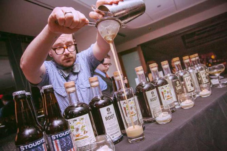 A Franklin-Mortgage bartender pours a speciality cocktail into a glass.