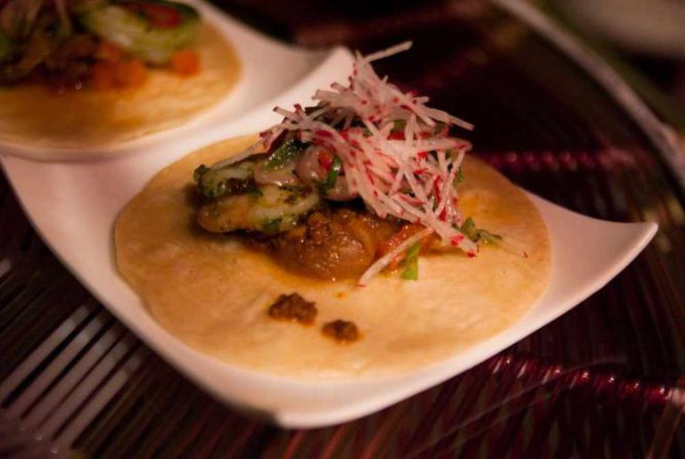 One of Garces' trademark fish tacos sits underneath a bed of chopped onions, guacamole and pickled vegetables.
