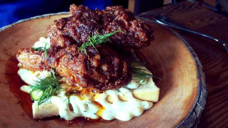 The hot chicken dish sits on a bed of brioche and cheese on top of a wooden plate at Fat Ham.