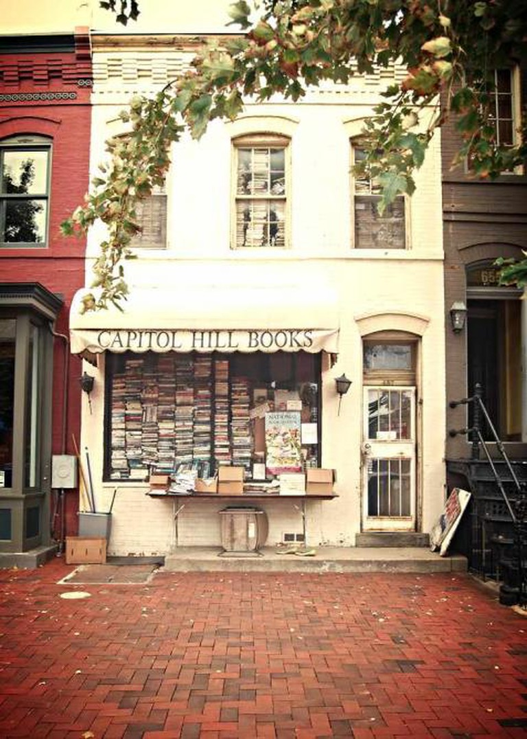 The outside facade of Capitol Hill Books with its towers of books seen through the windows.