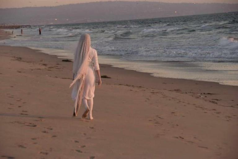Veiled woman on a beach