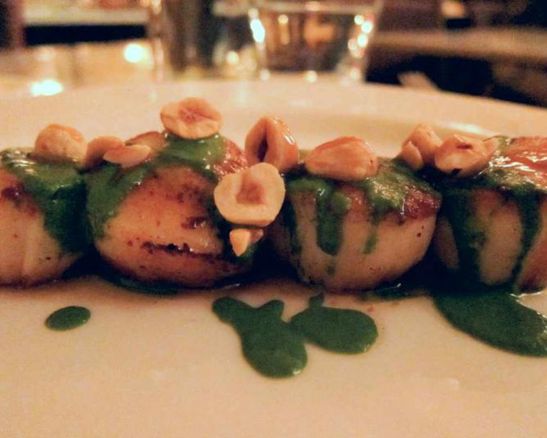 A dish of scallops is lightly coated with sherry scallop jus and sunchoke puree.