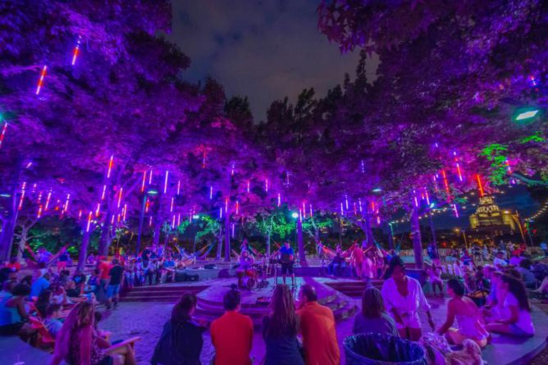 The lights of Spruce Street Harbor Park cast a magical glow while visitors watch musicians play in the park's courtyard.