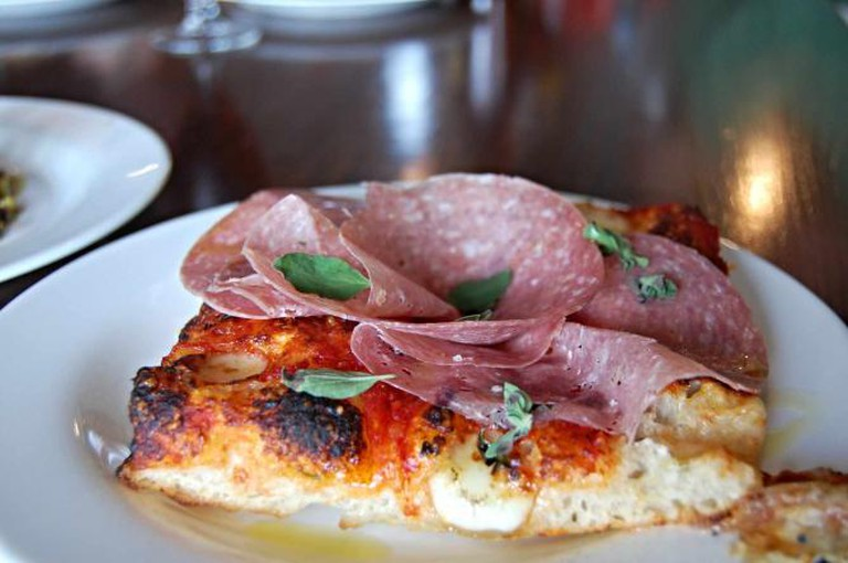 A piece of Neapolitan pizza with proscuitto at Pizzeria Vetri.