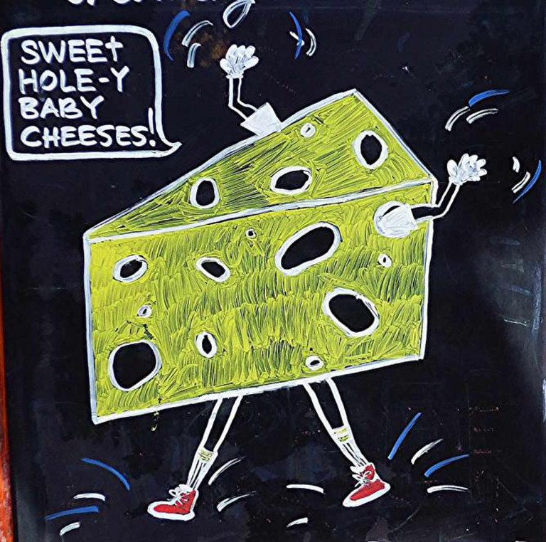 Cheese. Sidewalk sign for Sona Creamery and Wine Bar