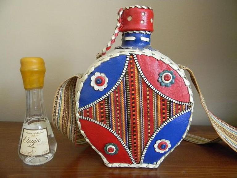 Bottle of Quince Rakija, beside Serbian traditional flask
