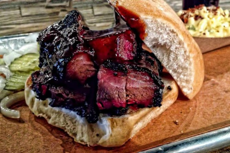 The smoked beef brisket sandwich with house sauce and a side of pickles and onions at Pecan Lodge is one of the best in Dallas.