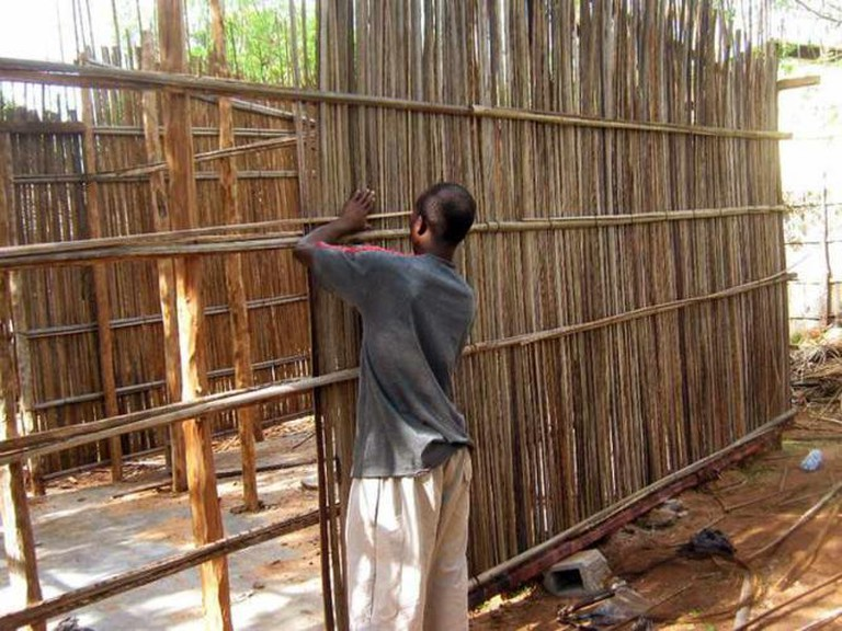 Mozambique walls being constructed using coconut palm spined stacked vertically | © Lauren Fox
